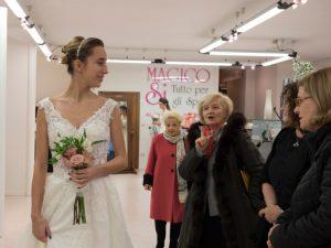 Sposa che sfila sorridente con abito e bouquet