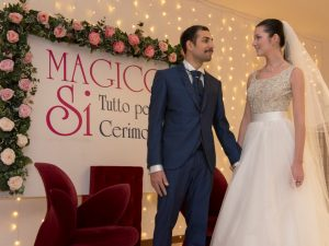 Coppia di sposi con abiti magico si e cornice di fiori